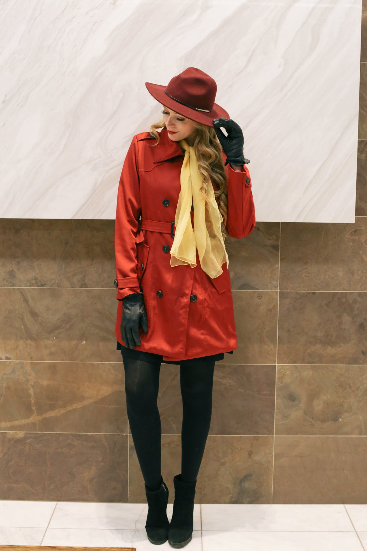 Carmen Sandiego DIY Halloween Costume: wearing a red trench coat, red fedora and yellow scarf.