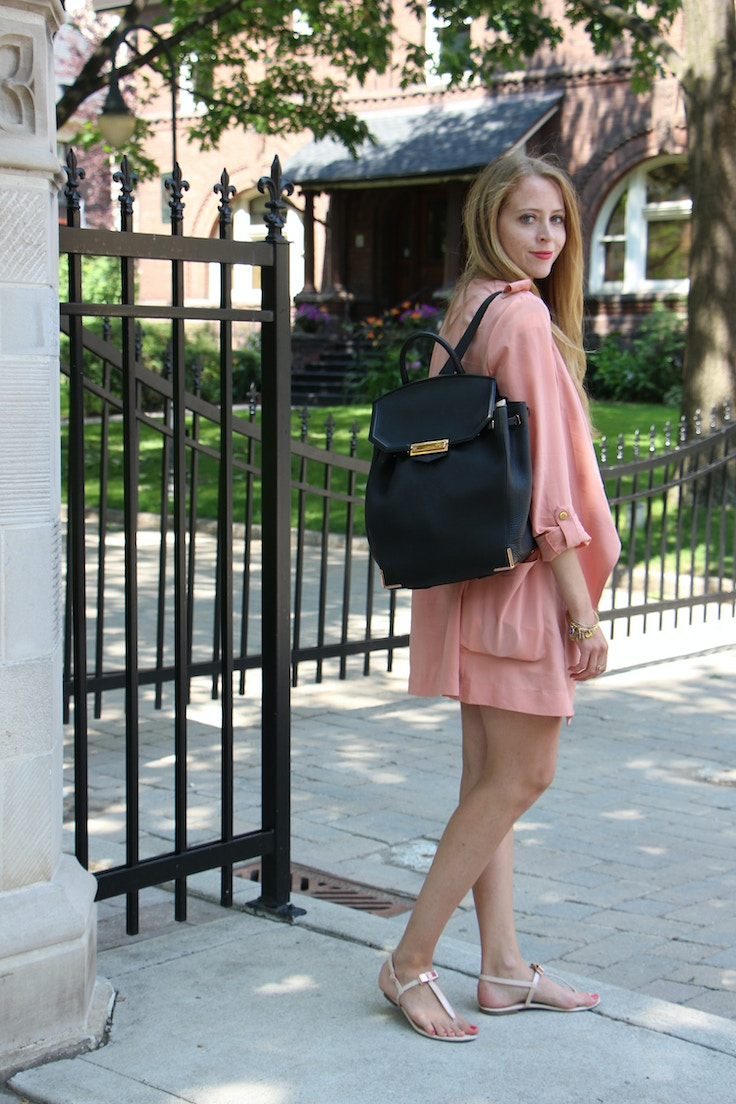 pink trench coat and black backpack