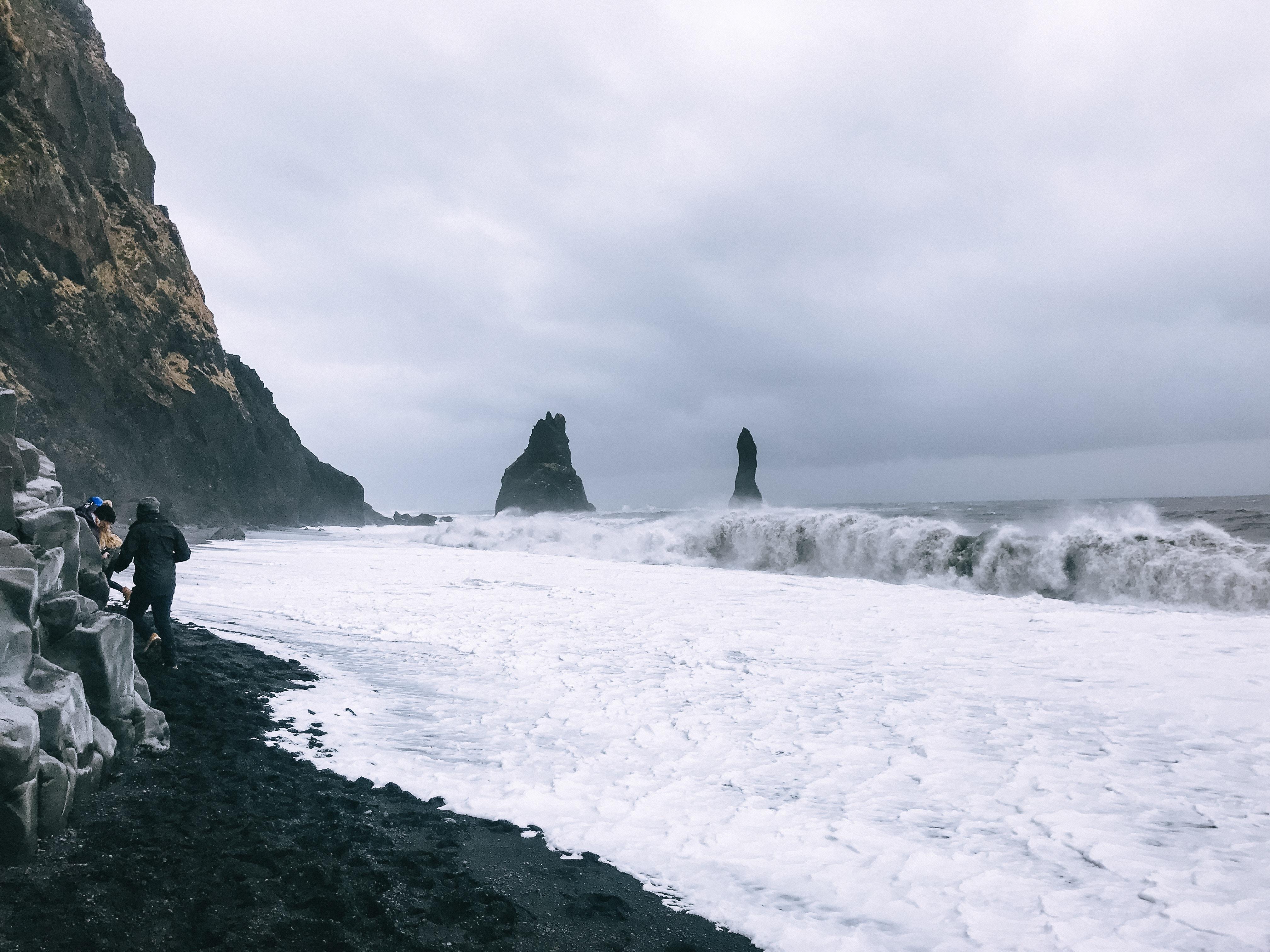 Powerful waves crashing the shores at Reynisfjara black sand beach in Vik, Iceland.