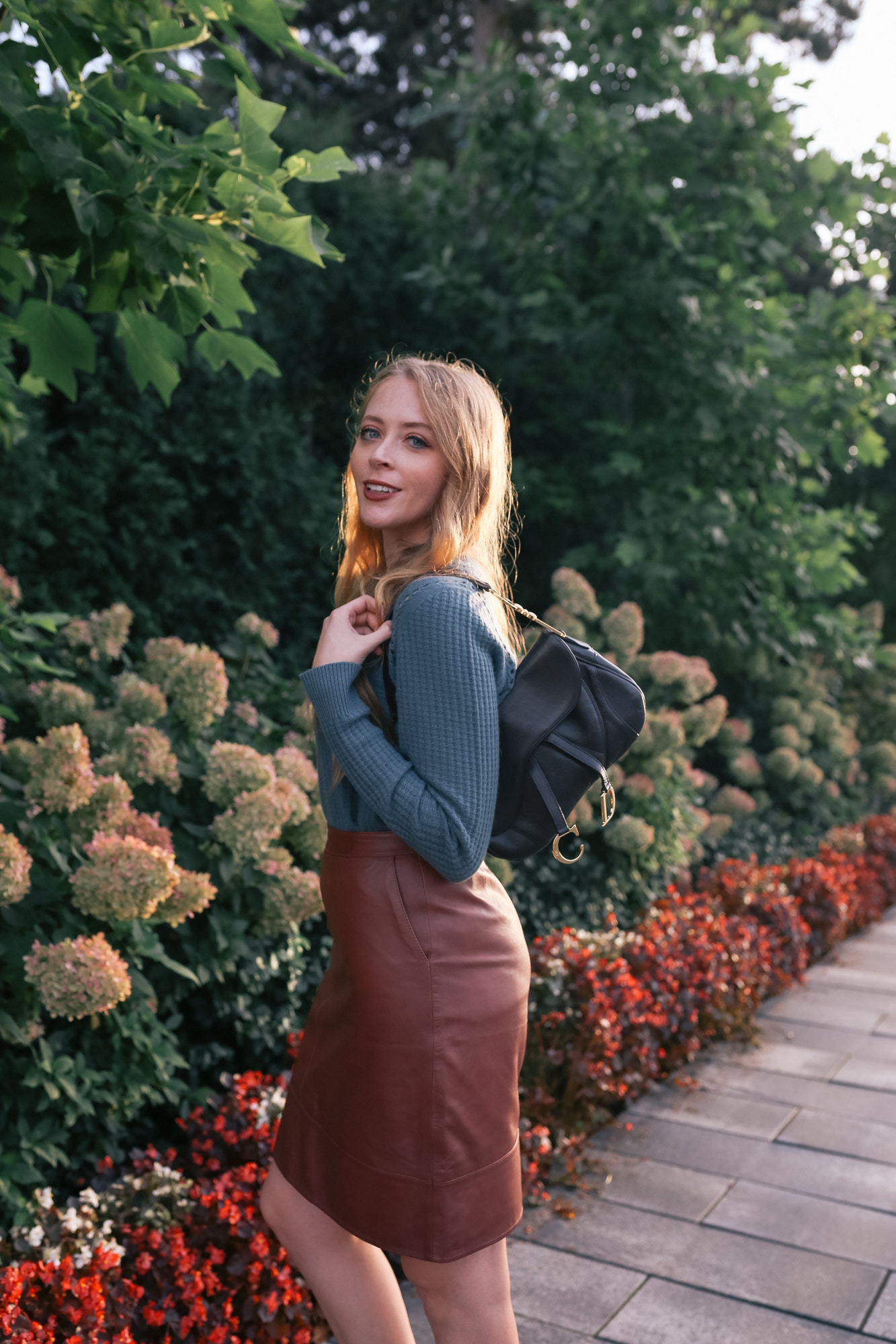 How I styled the Dior Saddle Bag: wearing a teal cashmere sweater, and leather skirt for a chic casual look.