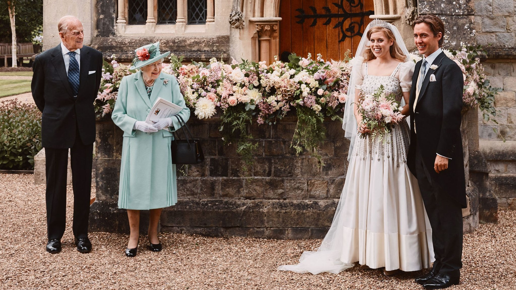 Queen Elizabeth and Prince Phillip stand socially distanced from the young bride and groom, Princess Beatrice of York and Edoardo Mapello Mozzi at their private ceremony in Windsor.