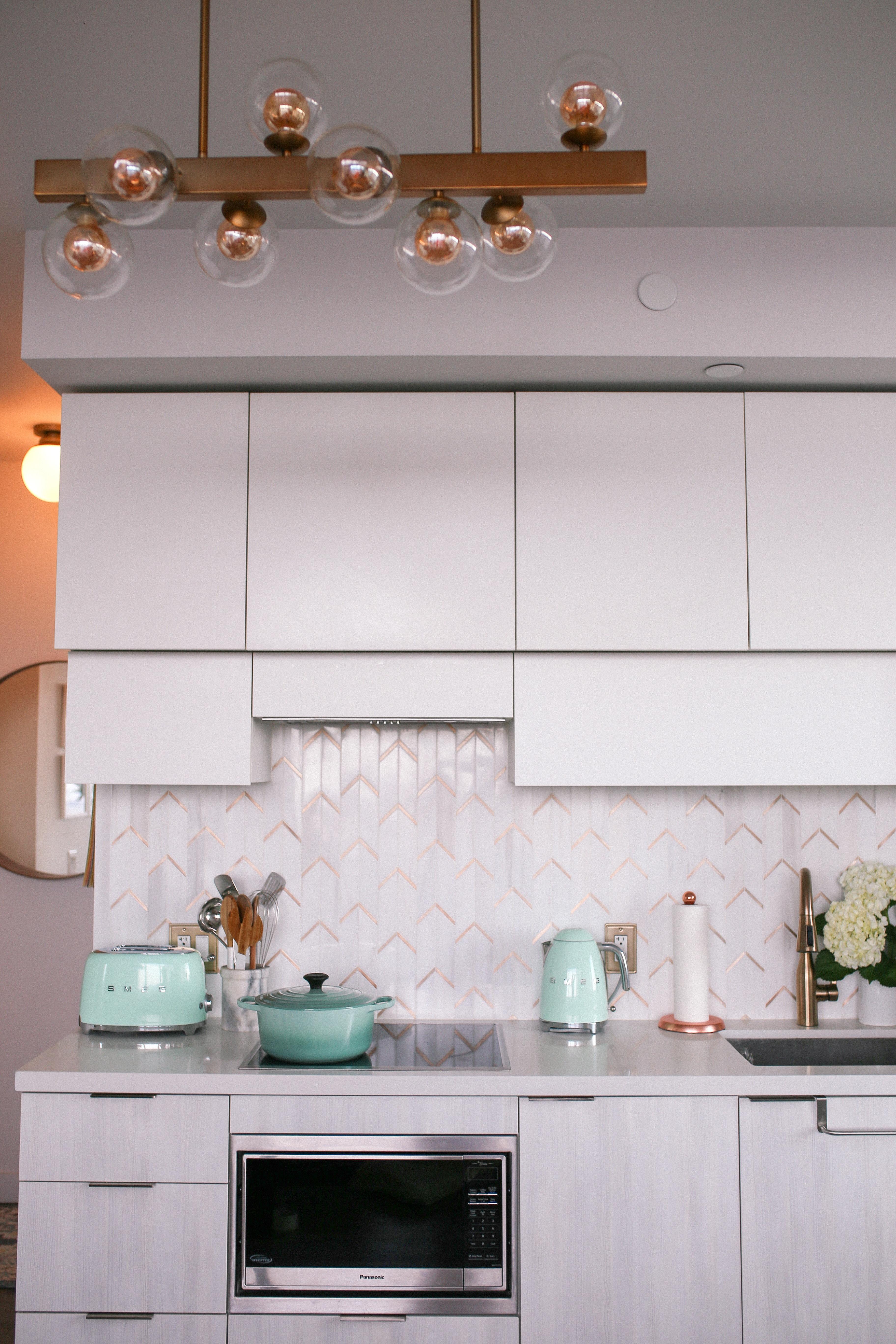 Condo-friendly ktichen makeover featuring a marble chevron backsplash with metal details, Smeg pastel green appliances, Le Creuset and a Delta Champagne Bronze faucet.